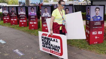 Una mujer retira carteles tras la cancelación del Gran Premio de Australia de Fórmula1 en Melbourne, el viernes 13 de marzo de 2020, debido al brote de coronavirus.