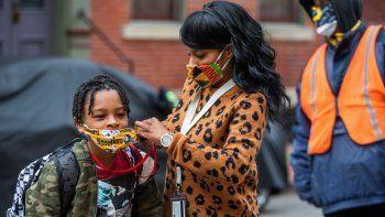 Jenea Edwards, de North Side, ayuda a su hijo Elijah, de nueve años y estudiante de tercer grado de primaria, a colocarse la mascarilla antes de ingresar a la escuela privada.