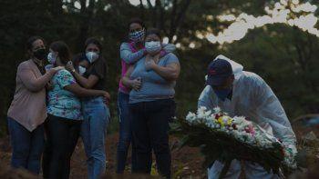Familiares de una víctima de la enfermedad del nuevo coronavirus COVID-19 lloran mientras su ser querido es enterrado en el cementerio de Vila Formosa en Sao Paulo, Brasil, el 31 de marzo de 2021.