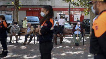 Algunos vecinos se sientan en un banco mientras los miembros de la Defensa Civil informan a los vecinos sobre las nuevas restricciones impuestas en el barrio bajo el cierre parcial de Usera, en Madrid, en la madrugada del 21 de septiembre de 2020.