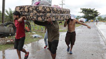 Vecinos se ayudan a transportar algunas pertenencias el lunes 16 de noviembre de 2020 para abandonar la zona donde se espera que toque tierra el huracán Iota, en San Manuel Cortés, Honduras.