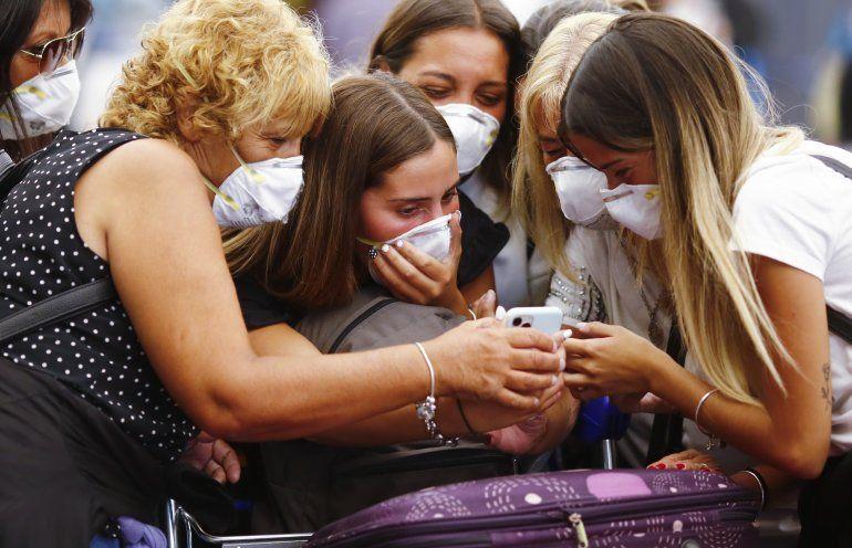 Viajeros con máscaras protectoras miran un teléfono inteligente en el Aeropuerto Internacional Ministro Pistarini