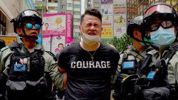 La policía detiene a un manifestante tras rociarle espray de pimienta durante una protesta en Causeway Bay antes de una marcha anual en Hong Kong, el 1 de julio de 2020.