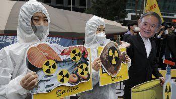 Activistas ambientales con una máscara del primer ministro japonés Yoshihide Suga protestan por la decisión de Japón de verter al mar agua de la planta nuclear de Fukushima, cerca de la embajada japonesa en Seúl, Corea del Sur, el martes 13 de abril de 2021.