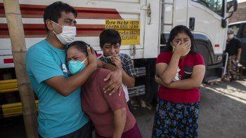 Familiares lloran mientras observan como operarios de la funeraria Piedrangel retiran el cuerpo de un pariente que se cree que murió a causa del nuevo coronavirus, en Lima, Perú, el 11 de mayo de 2020. Pese a las estrictas medidas para controlar el virus, Perú es uno de los países más afectados por la pandemia.