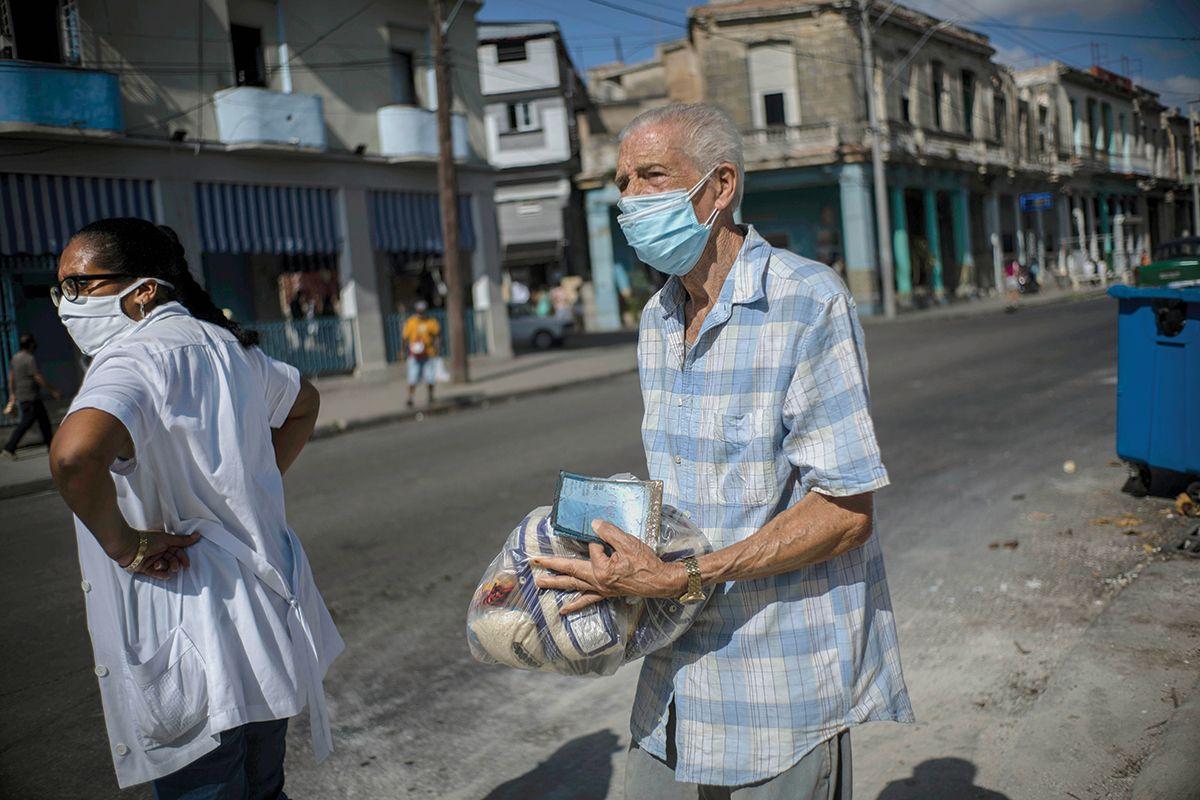 Un cubano lleva entre sus manos una ración mensual de alimentos básicos subsidiados por el régimen.