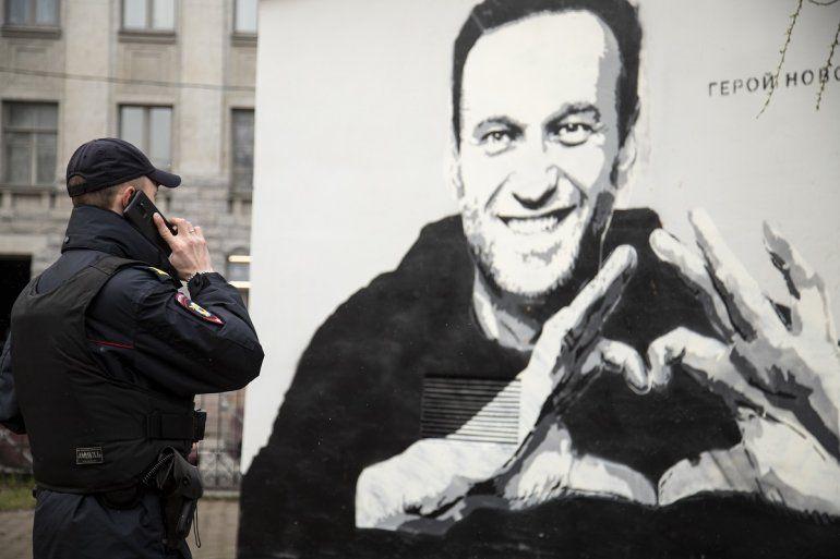 Un agente de policía habla por teléfono cerca de un grafiti con la imagen del encarcelado líder opositor ruso Alexei Navalny