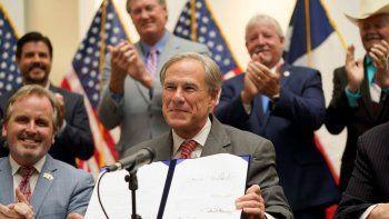 El gobernador de Texas, Greg Abbott, muestra la iniciativa SB1 que reforma la ley electoral estatal después de firmarla el martes 7 de septiembre de 2021.