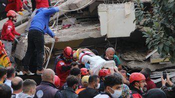 Rescatistas y voluntarios locales llevan a una víctima herida en una camilla desde un edificio derrumbado después de que un poderoso terremoto azotara la costa occidental de Turquía y partes de Grecia, en Izmir, el 30 de octubre de 2020.