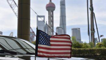 Una bandera de Estados Unidos ondea en un auto del consulado, delante de los edificios del distrito financiero de Lujiazui, en el exterior del hotel donde se alojan los negociadores comerciales de EEUU durante los contactos con sus homólogos chinos, en Shanghái, el 31 de julio de 2019.