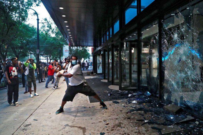 Un manifestante rompe cristales el viernes 29 de mayo de 2020 en la sede de la cadena CNN en Atlanta
