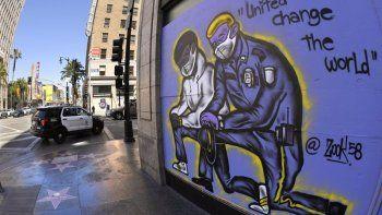 Un mural dibujado en los tablones que protegen un negocio mientras una patrulla del Departamento de Policía de Los Ángeles pasa por el lugar, el martes 9 de junio de 2020, en la sección de Hollywood, en Los Ángeles.
