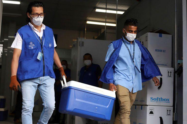 Trabajadores del Ministerio de Salud cargan hieleras con vacunas para el COVID-19 que el gobierno de El Salvador donó a Honduras mientras cargan camiones que partirán de San Salvador