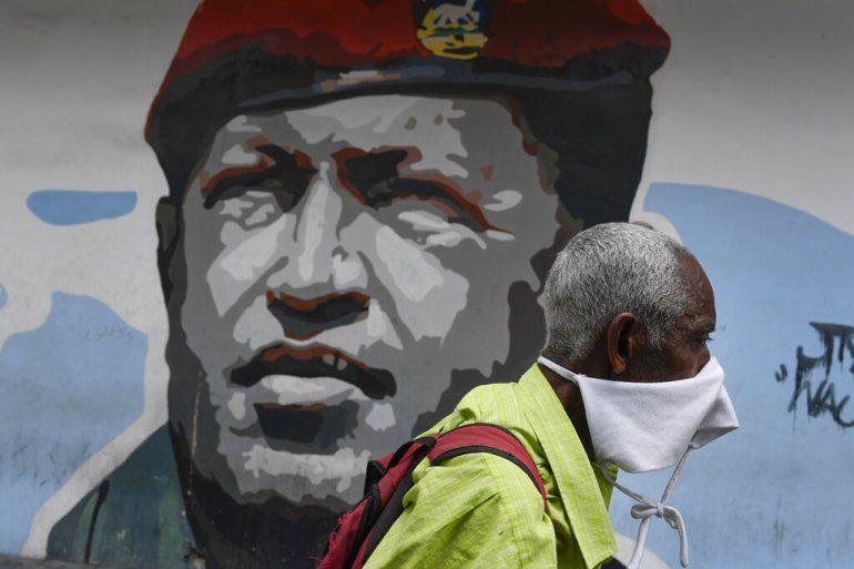 Un hombre que porta una mascarilla improvisada para protegerse del coronavirus camina el domingo 29 de marzo de 2020 junto a un mural del fallecido Hugo Chávez