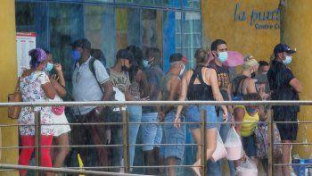 Con máscaras como precaución contra la propagación del nuevo coronavirus, la gente hace cola en la entrada de una tienda estatal de dólares en La Habana, Cuba.