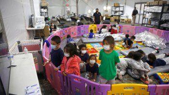 Niños migrantes de tres a nueve años de edad juegan o miran televisión en una instalación del servicio de Aduanas y Protección Fronteriza de EEUU en Donna, Texas, el 30 de marzo del 2021.