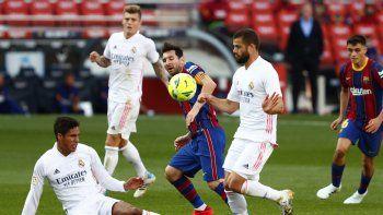 El delantero del Barcelona Lionel Messi (medio) pugna el balón con Raphael Varane y Nacho (derecha) del Real Madrid en el partido de La Liga española, el sábado 4 de octubre de 2020