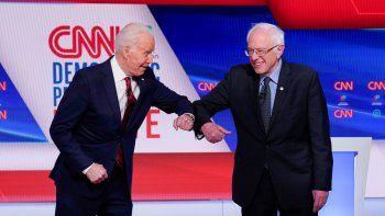 En esta foto del 15 de marzo del 2020, el ahora candidato presidencial demócrata Joe Biden, izquierda, y el senador Bernie Sanders que se identifica como socialista demócrata, se saludan antes del comienzo del debate presidencial demócrata en los estudios de la CNN en Washington.
