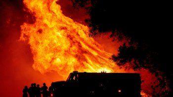 Los bomberos del condado de Butte observan cómo las llamas se elevan sobre su camión en el incendio Bear en Oroville, California, el 9 de septiembre de 2020.