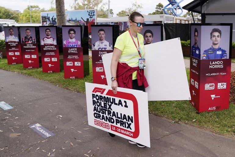 Una mujer retira carteles tras la cancelación del Gran Premio de Australia de Fórmula1 en Melbourne