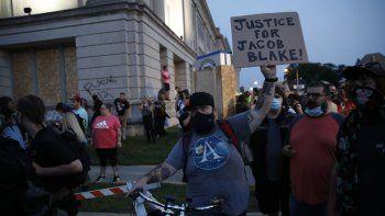 Manifestante sostiene un cartel mientras marchan frente a la Corte de Justicia del Condado durante las manifestaciones contra el tiroteo a Jacob Blake en Kenosha, Wisconsin, el 25 de agosto de 2020.