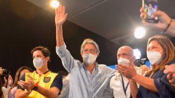 El candidato presidencial ecuatoriano Guillermo Lasso (R) saluda a simpatizantes mientras celebra su victoria luego de conocer los resultados preliminares de la segunda vuelta electoral en el Centro de Convenciones de Guayaquil, Ecuador, el 11 de abril de 2021.