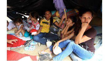 Colombianos que han retornado voluntariamente desde Venezuelapermanecen con sus pocas pertenencias bajo un plástico en la Playa, sector de La Parada, Colombia. (EFE)