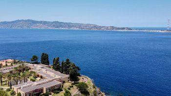 Una vista aérea general muestra la costa siciliana hacia el cabo Torre Faro, sobre el Estrecho de Messina, tomada desde las afueras de la ciudad de Scilla, en la región de Calabria en el sur de Italia, el 7 de julio de 2020.