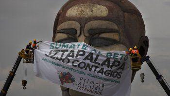 Trabajadores de la ciudad colocan una mascarilla gigante con un texto escrito en español que dice Súmeta al reto, Iztapalapa cero contagios, en el museo Cabeza de Juárez en medio de la pandemia de COVID-19, en Iztapalapa, Ciudad de México, el miércoles 12 de agosto de 2020.