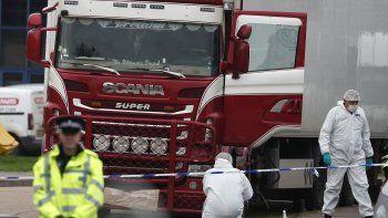 Fotografía de archivo del miércoles 23 de octubre de 2019 de policías forenses, a la derecha, recolectando pruebas después de descubrirse un camión con decenas de migrantes muertos, en Grays, Inglaterra.