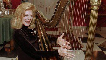 En esta fotografía de archivo del martes 12 de diciembre de 1995, la cantante Phyllis McGuire, la más joven de The McGuire Sisters, toca un arpa en su casa de Las Vegas.