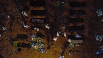 Foto de archivo aéreo tomada el 17 de abril de 2021 que muestra a trabajadores con equipo de protección como medida preventiva contra la propagación de la nueva enfermedad del coronavirus, COVID-19, enterrando ataúdes en el cementerio de Vila Formosa en Sao Paulo, Brasil. La segunda ola de la pandemia ha convertido a Brasil en el país con mayor mortalidad por COVID-19 en el continente y el hemisferio sur, informó el 20 de abril de 2021 a la AFP el investigador brasileño José Eustaquio Alves, profesor retirado del Instituto Brasileño de Geografía y Estadística (IBGE).