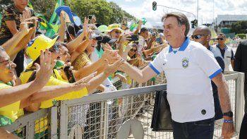 El presidente brasileño Jair Bolsonaro saluda a sus partidarios frente al Palacio de Planalto, después de manifestaciones contra el Congreso Nacional y la Corte Suprema, en Brasilia, el 15 de marzo de 2020.