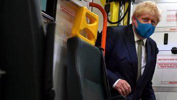 El primer ministro de Gran Bretaña, Boris Johnson, sube a una ambulancia con una mascarilla puesta durante una visita a la sede del Servicio de Ambulancia de Londres NHS Trust en Londres, el lunes 13 de julio de 2020.