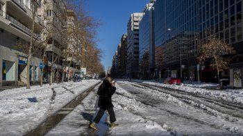 Una mujer cruza una calle nevada en Madrid, España, 11 de junio de 2020. La capital española trata de volver a ponerse en marcha tras una nevada récord que paralizó una gran parte del centro del país.