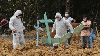 En esta imagen, tomada el 16 de abril de 2020, enterradores, vestidos con equipos de protección, preparan una tumba en el cementerio Nossa Senhora Aparecida para una mujer que se cree que murió por COVID-19, en Manaos, en el Amazonas de Brasil