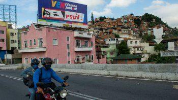La gente pasa en bicicleta frente a una valla publicitaria con propaganda política que representa los ojos del fallecido presidente venezolano Hugo Chávez, en Caracas el 2 de diciembre de 2020 antes de las elecciones parlamentarias en el país. Venezolano celebrará elecciones legislativas el 6 de diciembre.