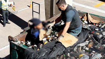 Una imagen publicada por la Guardia Civil española el 22 de febrero de 2021 muestra a un miembro de la Guardia Civil española descubriendo a un migrante escondido en un contenedor lleno de vidrios rotos para reciclar en el puerto del enclave español de Melilla en la costa norte de Marruecos, en febrero 19 de febrero de 2021.