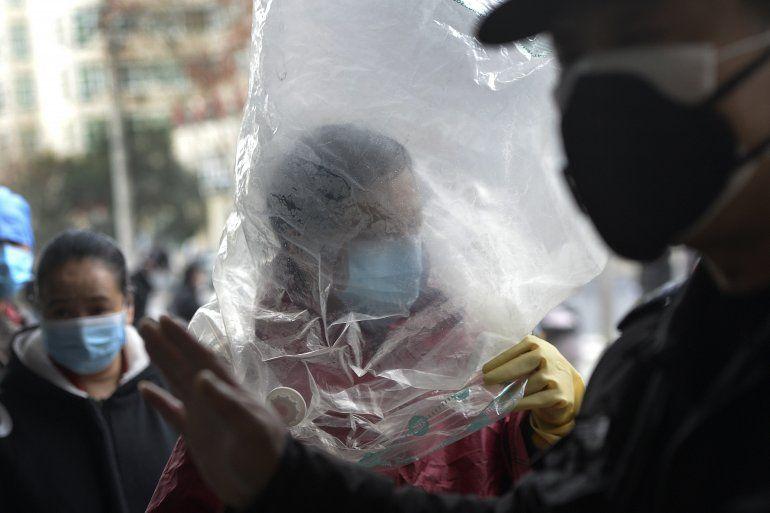 Un hombre cubre su rostro con una mascarilla y una bolsa de plástico