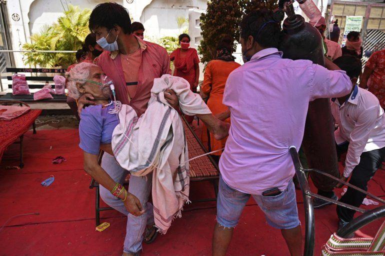 Un miembro de la familia lleva a un paciente que respira con la ayuda del oxígeno que le proporciona un Gurdwara