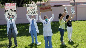 El doctor Franklyn Rocha Cabrero, izquierdo, la doctora Claudia Alvarez, centro, y otros protestan por las condiciones en las que el Servicio de Control de Inmigración y Aduanas de Estados Unidos tiene detenidos a inmigrantes en el centro te transición Broward durante la pandemia del nuevo coronavirus, el viernes 1 de mayo de 2020 en Pompano Beach, Florida.
