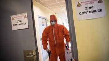 Para frenar la propagación del coronavirus en Francia, un trabajador de la salud usa un rociador para desinfectar el pasillo de un gimnasio utilizado como centro de descontaminación para trabajadores sanitarios y médicos a domicilio, el 6 de abril de 2020, en Trignac, oeste de ese país, es el día 21 de un encierro en Francia.