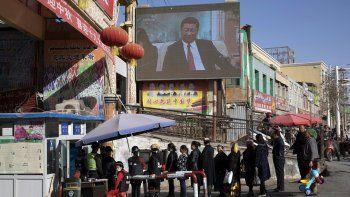 En esta imagen de archivo del 3 de noviembre de 2017, vecinos esperando en fila en un control de seguridad en el bazar Hotan, donde una pantalla muestra al presidente de China, Xi Jinping, en Hotan, en la región occidental china de Xinjiang.