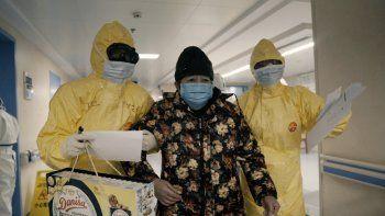 Una mujer mayor con COVID-19, centro, es acompañada por dos enfermeras tras ser admitida en un hospital en Wuhan, China, en una escena del documental 76 Days. El filme realizado en hospitales de Wuhan captura el horror local antes de que se volviera una pesadilla mundial.