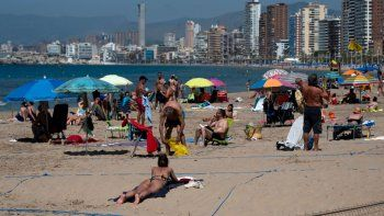 Turistas quetoman el sol en áreas designadas y separadas con cuerdas disfrutan de un día en la playa de Poniente en Benidorm, el 21 de junio de 2020, un día después de que las playas reabrieran al turismo tras tres meses de cierre debido al coronavirus.