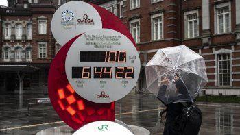 Un hombre toma una foto de un reloj de cuenta regresiva para los Juegos Olímpicos y Paralímpicos de Tokio 2020 100 días antes de la ceremonia de apertura, frente a una estación de Tokio en Tokio el 14 de abril de 2021.