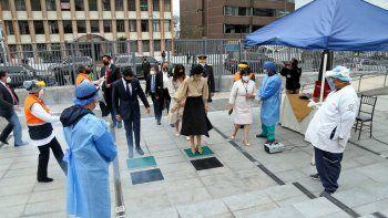 Folleto publicado por la Asamblea Nacional de Ecuador que muestra a la nueva Vicepresidenta de Ecuador, María Alejandra Muñoz (C) desinfectando sus zapatos contra la propagación del nuevo coronavirus COVID-19 al llegar a su inauguración en la Asamblea Nacional en Quito el 22 de julio, 2020.