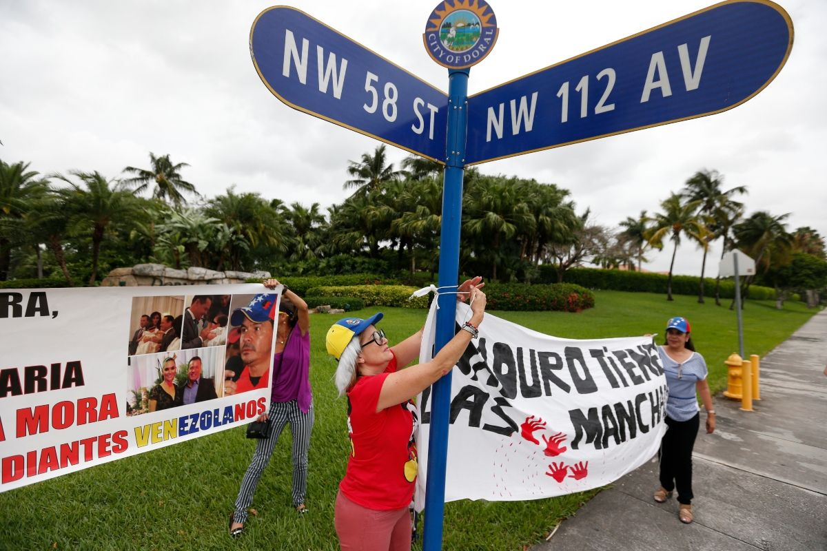 En esta foto del 24 de mayo de 2017, los manifestantes cuelgan una pancarta afuera de una comunidad cerrada donde se cree que un presunto testaferro del prominente gobernador chavista Gregorio Vielma Mora vive con su esposa, la reina de belleza, en un suburbio de Miami conocido como Little Venezuela, en Doral. , Florida.