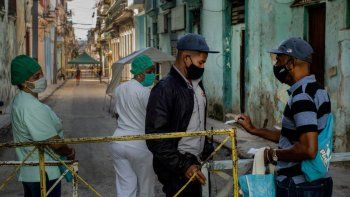 Un residente muestra su identificación a un oficial de policía que está limitando el acceso a un vecindario como una forma de frenar la propagación de la pandemia de COVID-19, mientras enfermeras están detrás en La Habana, Cuba.