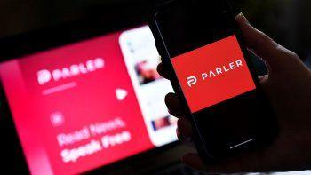 En esta foto de archivo tomada el 1 de julio de 2020, muestra el logotipo de la aplicación de redes sociales de Parler en un teléfono inteligente con su sitio web.